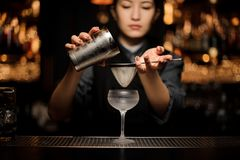 Female bartender prepares alcohol cocktail with shaker and sieve. Beautiful female bartender prepares an alcohol cocktail with a metal shaker and sieve at bar royalty free stock image