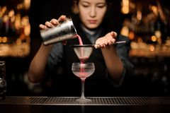 Female bartender preparing the alcohol cocktail with shaker and sieve. Beautiful female bartender preparing the alcohol cocktail with a metal shaker and sieve at stock image