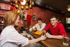 Female bartender serving beer to men at bar counter Stock Images