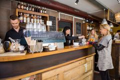 Female Bartender Serving Coffee To Customer At Stock Image