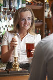 Female Bartender Serving Drink To Male Customer Royalty Free Stock Image