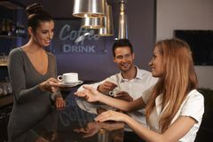 Female bartender serving young couple in bar Stock Photos
