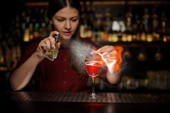Female bartender sprinkling a cocktail glass with Aperol syringe cocktail with a peated whisky and making a smoky note on the bar. Female bartender sprinkling a Stock Photography