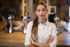 Female bartender standing with arms crossed in bar. Portrait of female bartender standing with arms crossed in bar Royalty Free Stock Image