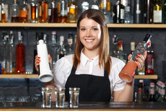 Female bartender at work. Portrait of a pretty bartender standing smiling and holding two bottles of liquors, shelves full of bottles with alcohol on the Royalty Free Stock Photography