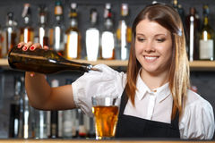 Female bartender at work. Portrait of a pretty bartender standing smiling and pouring a drink from a bottle, shelves full of bottles with alcohol on the Royalty Free Stock Images