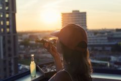 A female in a baseball cap eats a huge piece of pizza on sunset city background. Concept stock images
