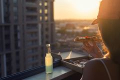 A female in a baseball cap eats a huge piece of pizza on sunset and city background. Concept stock image