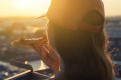 A female in a baseball cap eats a huge piece of pizza on sunset and city background. Concept royalty free stock image