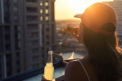 A female in a baseball cap eats a huge piece of pizza on sunset and city background. Concept stock photography