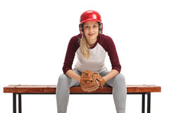 Female baseball player with a catcher glove and a helmet sitting Royalty Free Stock Photography