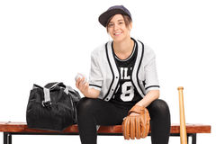 Female baseball player seated on a bench Royalty Free Stock Image