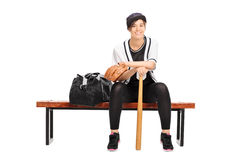 Female baseball player sitting on a bench Stock Photo