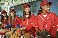 Female Baseball Players Sitting In A Row Royalty Free Stock Images