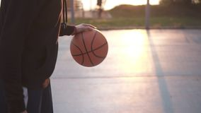 Female basketball basketball player bouncing the ball. Slow motion shot of basketball player training on the outdoors. Court. Morning sun shines on the stock footage