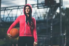 Female basketball player training outdoors on a local court Royalty Free Stock Images