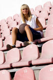 Female basketball player waiting for a match. Teenage blond girl waiting for a basketball match in the fan area royalty free stock photo