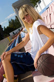 Female basketball player waiting for a match. Teenage blond girl waiting for a basketball match in the fan area stock photos
