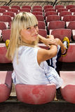 Female basketball player waiting for a match. Teenage blond girl waiting for a basketball match in the fan area Stock Images