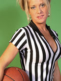 Female Basketball Referee. A portrait of a pretty young blond wears a professional basketball referee's shirt and holds a basketball Stock Photo