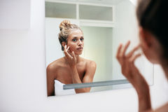 Female in bathroom looking into the mirror Stock Image