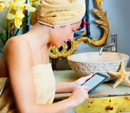 Female in bathroom reading ebook tablet Royalty Free Stock Photos