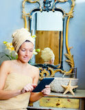 Female in bathroomreading ebook tablet Royalty Free Stock Images