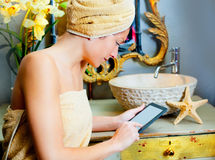 Female in bathroomreading ebook tablet Royalty Free Stock Photography