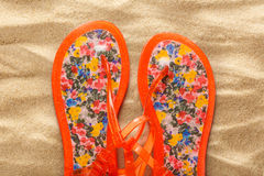 Female beach sandals on sand background royalty free stock photos