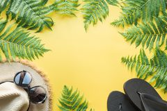 Female beach straw hat, sunglasses, flip flops on yellow. Top view. Summer travel concept. Female beach straw sunhat, sunglasses, flip flops on punchy yellow stock image