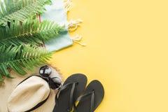 Female beach straw sunhat, sunglasses, flip flops on yellow. Top view. Summer travel concept. Female beach straw sunhat, sunglasses, flip flops on punchy yellow stock image