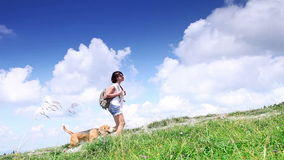 Female with beagle dog walking in mountains with clouds stock footage