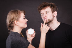 Female beautician apply cream on male mouth. Stock Photos