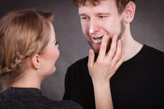 Female beautician apply cream on male mouth. Hygiene and skincare concept. Young blonde female beautician cosmetician apply cream on male mouth lips. Woman and Stock Photo