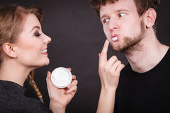 Female beautician apply cream on male mouth. Stock Image