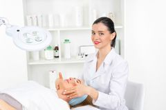 Female beautician doctor with patient in wellness center. Professional cosmetologist make procedure to beautiful girl in stock photography