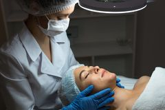 Female beautician doctor with patient in wellness center. Professional cosmetologist make procedure to beautiful girl in stock photo