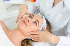 Female beautician doctor with patient in wellness center. Professional cosmetologist make procedure to beautiful girl in royalty free stock images