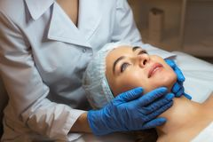 Female beautician doctor with patient in wellness center. Professional cosmetologist make procedure to beautiful girl in. Cosmetology cabinet or beauty parlor stock image