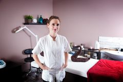 Female beautician in her beauty and massage salon. Female beautician in her new modern beauty and massage salon. Smiling and proud Royalty Free Stock Photo