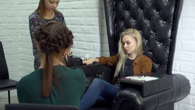 Female beauticians do different procedures and services in beauty salon. Pedicures and manicures do two workers to a beauty salon blonde girl sitting in luxury stock video footage