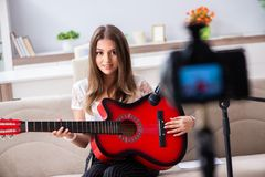 The female beautiful blogger playing guitar. Female beautiful blogger playing guitar royalty free stock images