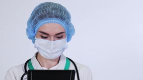 Female doctor using a tablet computer in a hospital. Female beautiful doctor in surgical mask and medical cap using a tablet computer on the white background and stock video footage