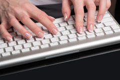Female beautiful hands with classical French manicure are located over the computer keypad Royalty Free Stock Images