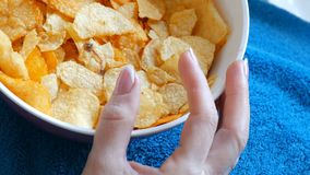 Female beautiful well-groomed hands with French manicure take potato chips from deep plate. Unhealthy food, fast food. Female beautiful well-groomed hands with stock footage
