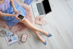 Female beauty blogger with smartphone indoors. Top view royalty free stock photo