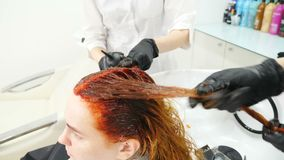 Female beauty concept. colorist and assistant dyeing and coloring client hair in barbershop. Hairdresser applying dye on. Hair with 4 hands technic. hd stock video footage