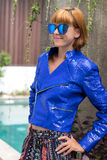 Female beauty concept. Portrait of fashionable young girl in blue luxury snakeskin python jacket and sunglasses posing Royalty Free Stock Image
