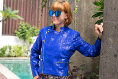 Female beauty concept. Portrait of fashionable young girl in blue luxury snakeskin python jacket and sunglasses posing Stock Images