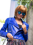 Female beauty concept. Portrait of fashionable young girl in blue luxury snakeskin python jacket and sunglasses posing Royalty Free Stock Images